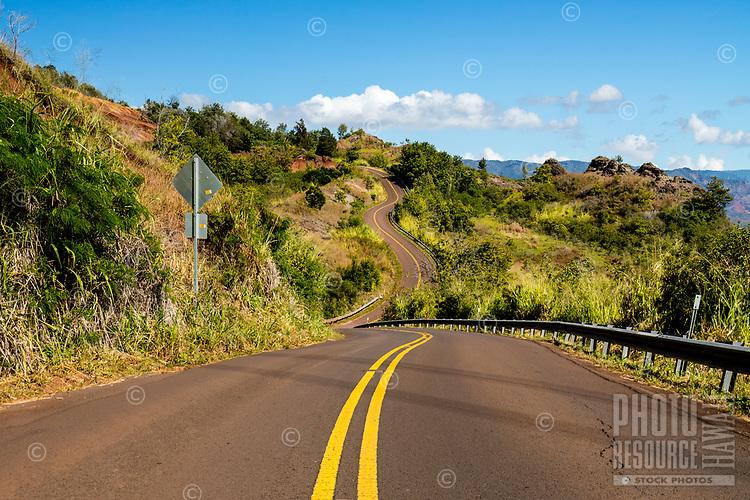 Waimea Canyon Drive winds up a lush mountain scene as it enters into Waimea Canyon State Park, Kaua'i.