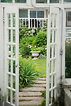 View from inside the Victorian-looking greenhouse behind the farmhouse on this property about one hour north of Seattle in the Skagit Valley, looking out the path to the Sissinghurst-style white garden that includes white delphiniums, white peonies, white climbing and shrub roses, and bleeding heart, among others.  The greenhouse itself was salvaged and reclaimed for use from an arboretum in the region. Garden design by Toni Christianson, Christianson's Nursery