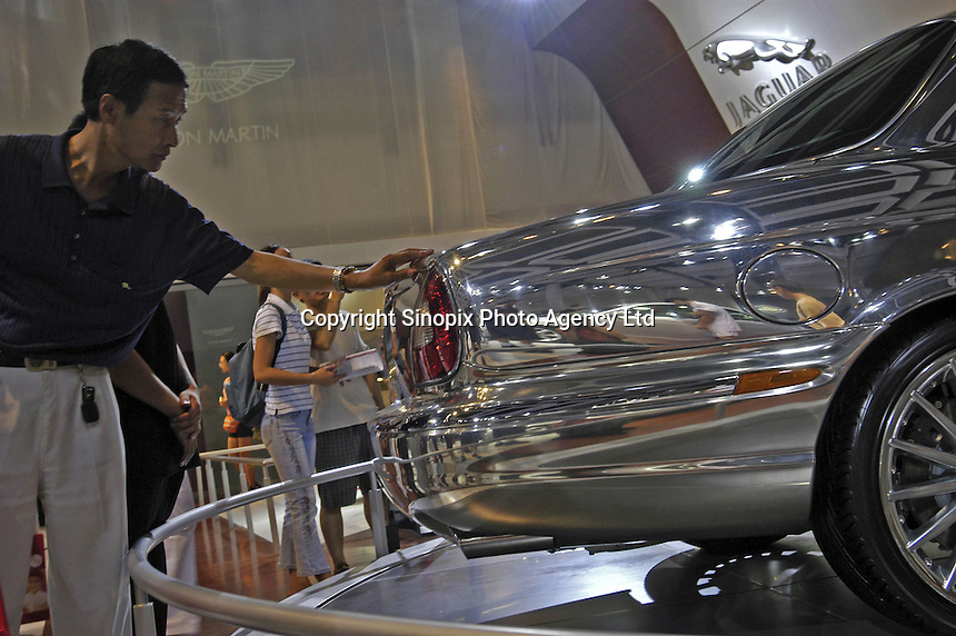 A visitors touchs a Jaguar XJR at the Auto China 2004 exhibition in Beijing, China..