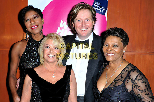 NATALIE COLE, ELAINE PAIGE, TIM HOLDER &amp; DIONNE WARWICK <br /> attends The Hunger Project Concert after party as part of World Hunger Day 2011 at the Park Plaza Hotel in London, England, UK, January 9th, 2011.<br /> half length black sleeveless dress velvet tall short  beaded sparkly bow tie tuxedo tux <br /> CAP/MAR<br /> &not;&copy; Martin Harris/Capital Pictures