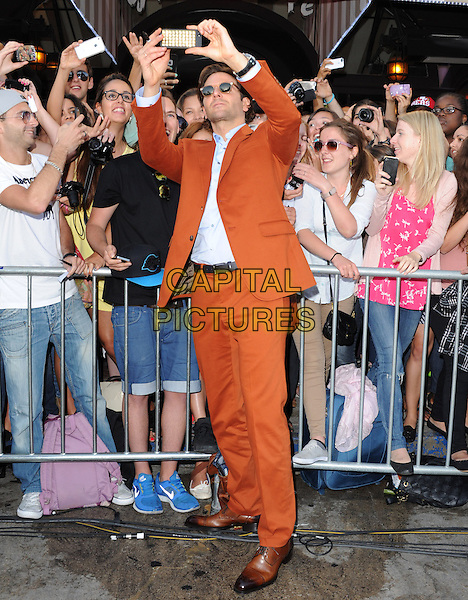 "Bradley Cooper.""The Hangover Part III"" Los Angeles Premiere held at the Westwood Village Theater, Los Angeles, California, USA..May 20th, 2013.full length sunglasses shades mobile camera fans crowd posing orange suit blue shirt taking picture photographs                                                 .CAP/DVS.©DVS/Capital Pictures"