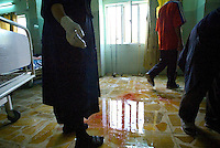 personnel cleans up after treating the wounded at the Iarmuk hospital on May 31 2004, in the outscorts of Baghdad. the blast that wounded him  claimed to damege the road near the judgement consular. the number of casualties is uncertain but is not less then three