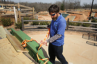 NWA Democrat-Gazette/DAVID GOTTSCHALK Jonathan Guyll, wit the city of Rogers Parks and Recreation Department, uses a ratchet strap to secure timber in the back of a trailer Friday, March 9, 2018, at the Railyard in Rogers. Located near downtown Rogers, the park received it's name   because of it's proximity to the Arkansas Missouri Railroad and the use of repurposed train and track parts.