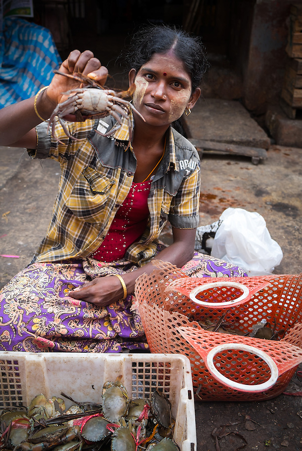 YANGON, MYANMAR - CIRCA DECEMBER 2013: Woman selling crab in the Yangon street market.
