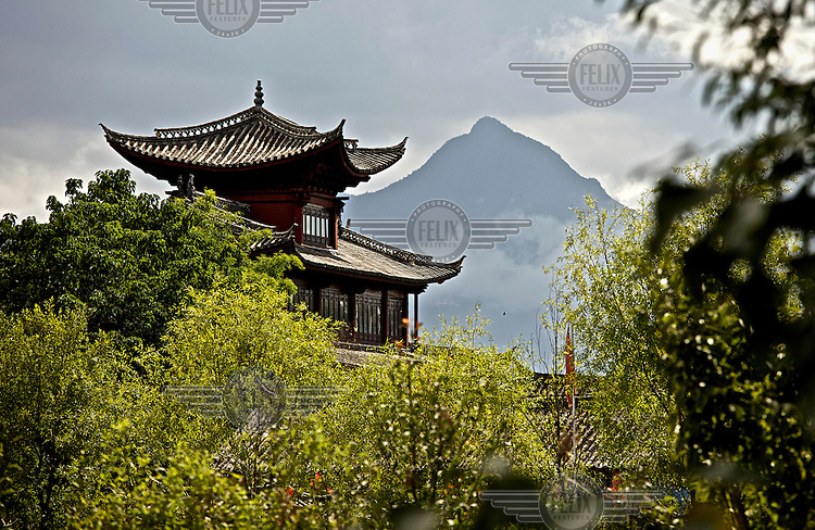 Yulong Mountain looms over one of the ancient buildings in Lijiang a town whose historic buildings are a major tourist attraction and an UNESCO World Heritage Site. /Felix Features