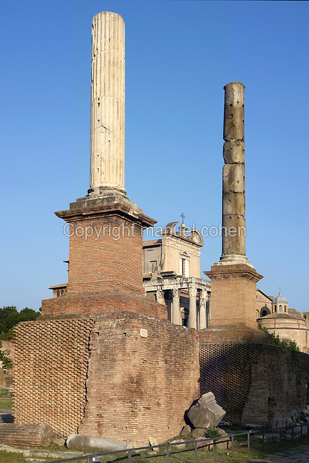 Temple of Antoninus and Faustina (141 AD) seen in between of the two Honorific Columns re-erected at the end of 19th century with grey granite and white marble, topping high brick bases dating 3rd century AD, Roman Forum, Rome, Italy, Europe.