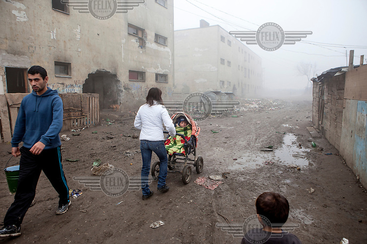 A woman pushes a child in a buggy along a muddy, unpaved street in the Roma settlement of 'Budulovskej Street'.
