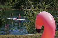 Switzerland. Canton Ticino. Tenero. Camping Campofelice. A boy and a girl, both campers, enjoy stand up paddle on the Verzasca river. Stand up paddle boarders stand on their boards and use a paddle to propel themselves through the water. A Giant X-Large Inflatable Flamingo Pool Float for adults and kids is laid on the grass. 19.07.2018 © 2018 Didier Ruef