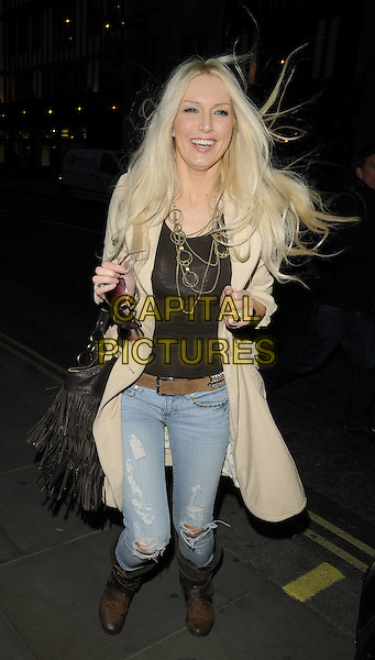 EMMA NOBLE.'Recognise' magazine Launch Party at Swarovski Crystallized, London, England. .April 13th, 2010 .full length jeans denim brown biker boots beige coat jacket top funny hands hair windy messy tassels fringed bag purse gold necklaces .CAP/CAN.©Can Nguyen/Capital Pictures.