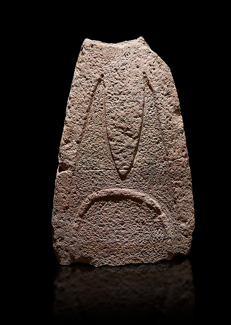 Late European Neolithic prehistoric Menhir standing stone with carvings on its face side. The representation of a stylalised male figure starts at the top with a long nose from which 2 eyebrows arch around the top of the stone. Excavated from Paule Luturru,  Samugheo. Menhir Museum, Museo della Statuaria Prehistorica in Sardegna, Museum of Prehoistoric Sardinian Statues, Palazzo Aymerich, Laconi, Sardinia, Italy. Black background.