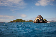An island made of weathered rock sits in the blue carribean waters off the shore of the US Virgin Islands.