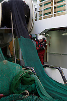 Deckhand supervising net being wound back onto net drum on deep sea trawler. Barents sea, Arctic Norway