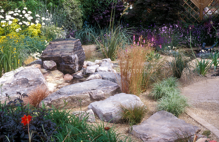 Rock garden with drought tolerant plants large stones for Using grasses in garden design