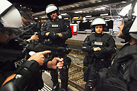 Switzerland. Canton Ticino. Lugano. Railway station. A group of police officers from TPO (Transport Police). All policemen and a policewoma wear the special riot police black uniforms and helmets. One officer holds in his hand a grenade launcher (40 mm BT08) and controls the weapon' s viewfinder, The police officers are standing on the platform and wait for the FC Luzern football club's supporters who will later leave in a chartered train. TPO (Transport Police) is the Swiss Federal Railways Police. Swiss Federal Railways (German: Schweizerische Bundesbahnen (SBB), French: Chemins de fer fédéraux suisses (CFF), Italian: Ferrovie federali svizzere (FFS)) is the national railway company of Switzerland. It is usually referred to by the initials of its German, French and Italian names, as SBB CFF FFS. 2.06.2017 © 2017 Didier Ruef