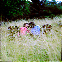 Couple sitting on Adirondack chairs in tall grass