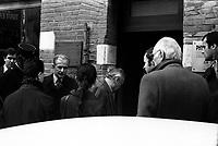 """""""Portai [Portay], Picard, Me Cathala, Me Bouscatel, Me Rastoul"""". 14 rue d'Aubuisson. 30 novembre 1976. Vue d'ensemble de Claude Birague arrivant à son domicile, est entouré du juge d'instruction, de ses avocats, policiers ; au 1er plan à gauche bras d'un photographe prenant une photo appuyé sur le toit d'une voiture. Cliché pris le jour d'une reconstitution judiciaire dans le cadre de l'affaire du meurtre de René Trouvé. Observation: Affaire René Trouvé-Birague : le 19 février 1976, le journaliste René Trouvé est assassiné d'une balle dans la tête, par deux inconnus, alors qu'il regagne son domicile au 33 rue Bayard."""
