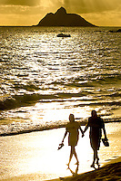 A walking couple is backlit by the the rising sun brightening the windward side of Oahu.  Moku Nui, the larger of the Mokulua Islands near Kailua is on the right.