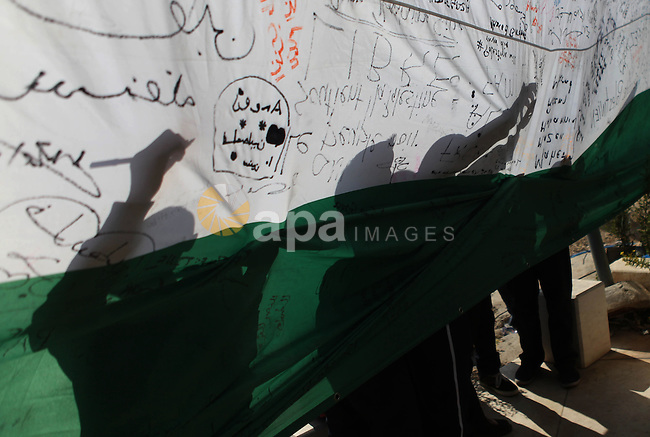 """people write on a Palestinian flag during an attempt to break the Guinness World Record for the """"largest Palestinian flag"""", in the West Bank city of Ramallah October 28, 2014. Photo by Shadi Hatem"""