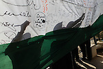"people write on a Palestinian flag during an attempt to break the Guinness World Record for the ""largest Palestinian flag"", in the West Bank city of Ramallah October 28, 2014. Photo by Shadi Hatem"
