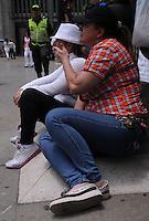 MEDELLÍN - COLOMBIA, 06-05-2014. Sandra Gutierrez, de blanco, decidió encadenarse a las puertas del Centro Administrativo de la Alpujarra en Medellín, Colombia, este martes 6 de mayo de 2014, tras el incumplimiento de la Personería de Medellín en referencia a las condiciones para desocupar su apartamento en el conjunto residencial Colores de Calasania, Medellín, el cual presenta fallas graves en su estructura y por tanto había sido evacuado el pasado 26 de abril de 2014./ Sandra Gutierrez (white)  decided to chain to the gates of La Alpujarra Administrative Center in Medellin, Colombia, Tuesday May 6, 2014, after the fail the conciliation with the Medeelin administration to vacate her apartment in the Colores de Calsania residencial comlex, Medellín, wich presents serious flaws in structure and therefore had been evacuated last April 26, 2014.  Photo: VizzorImage/Luis Rios/STR