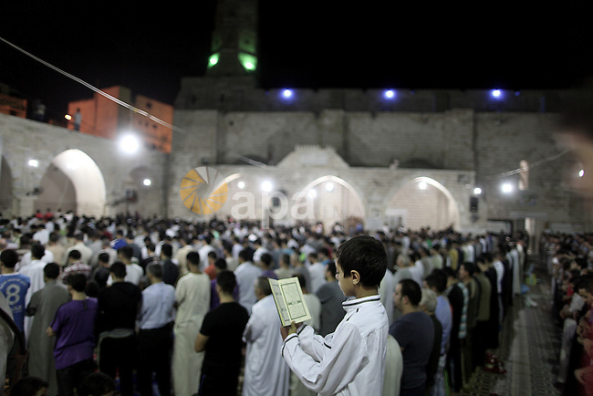 Palestinians pray during Laylat Al Qadr prayers on the 27th day of the holy fasting month of Ramadan at Al Emari mosque in Gaza City early on August 5, 2013. Muslims fasting in the month of Ramadan must abstain from food, drink and sex from dawn to dusk, when they break the fast with a meal known as Iftar. Photo by Ali Jadallah