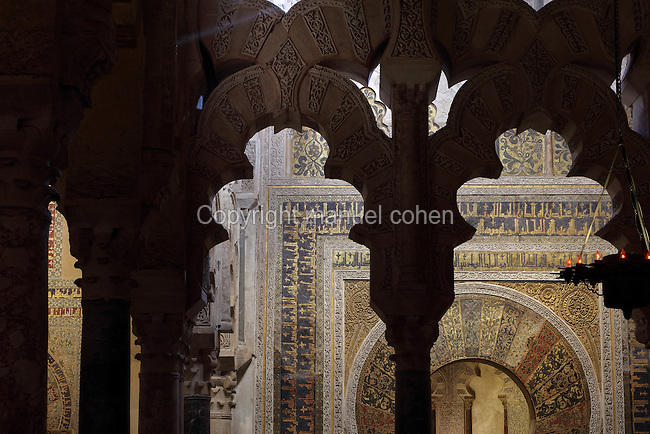 Looking through the maqsura, a richly decorated room with intricately carved interlacing fluted arches, redecorated under Al-Hakam II in 961, towards the mihrab portal, a horseshoe arch with rectangular surround or alfiz, richly decorated with tesserae (glass mosaic with gold or coloured backing) with vegetal designs and kufic inscriptions, in the Cathedral-Great Mosque of Cordoba, in Cordoba, Andalusia, Southern Spain. The first church built here by the Visigoths in the 7th century was split in half by the Moors, becoming half church, half mosque. In 784, the Great Mosque of Cordoba was begun in its place and developed over 200 years, but in 1236 it was converted into a catholic church, with a Renaissance cathedral nave built in the 16th century. The historic centre of Cordoba is listed as a UNESCO World Heritage Site. Picture by Manuel Cohen