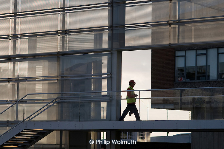 Pedestrian on a new footbridge over the Grand Union canal at Paddington Basin leading to The Point offcie development
