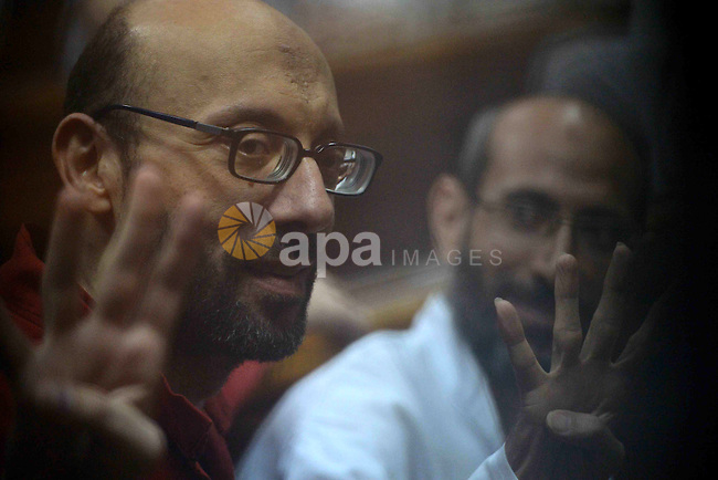 Egyptian Muslim Brotherhood defendants wave as they stand behind the bars during their trial, along with ousted Islamist president Mohamed Morsi (unseen) in Cairo on August 30, 2015. Cairo criminal court resumes today the trial of deposed president Mohamed Morsi and 10 others on charges of espionage and leaking classified documents related to the national security and the army to Qatar. Photo by Amr Sayed