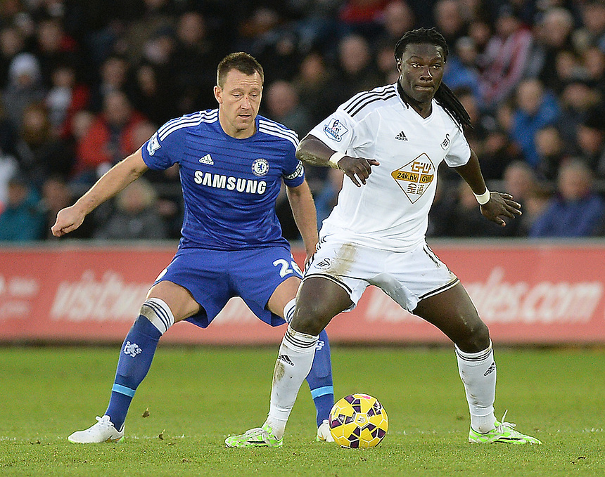 Chelsea's John Terry vies for possession with Swansea City's Bafetibis Gomis<br /> <br /> Photographer /Ashley CrowdenCameraSport<br /> <br /> Football - Barclays Premiership - Swansea City v Chelsea - Saturday 17th January 2015 - Liberty Stadium - Swansea<br /> <br /> &copy; CameraSport - 43 Linden Ave. Countesthorpe. Leicester. England. LE8 5PG - Tel: +44 (0) 116 277 4147 - admin@camerasport.com - www.camerasport.com