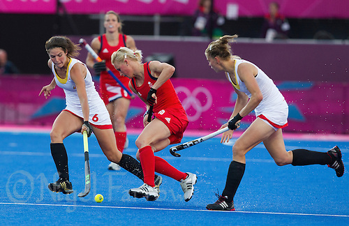 02 AUG 2012 - LONDON, GBR - Alex Danson (GBR) (centre) of Great Britain evades a challenge from Anouk Raes (BEL) (left) of Belgium during the London 2012 Olympic Games preliminary round hockey match between the two countries at the Riverbank Arena in the Olympic Park at Stratford, Great Britain .(PHOTO (C) 2012 NIGEL FARROW)
