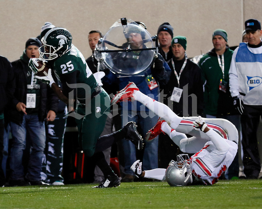 Michigan State Spartans wide receiver Keith Mumphery (25) catches a touchdown pass behind Ohio State Buckeyes cornerback Gareon Conley (19) during the first quarter of the NCAA football game at Spartan Stadium in East Lansing, Michigan on Nov. 8, 2014. (Adam Cairns / The Columbus Dispatch)