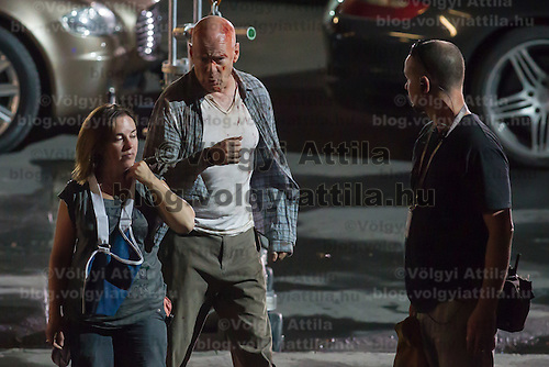US actor Bruce Willis (C) on set during a shooting of his next movie fifth in the Die Hard series titled Good Day to Die Hard in Budapest, Hungary on July 11, 2012. ATTILA VOLGYI