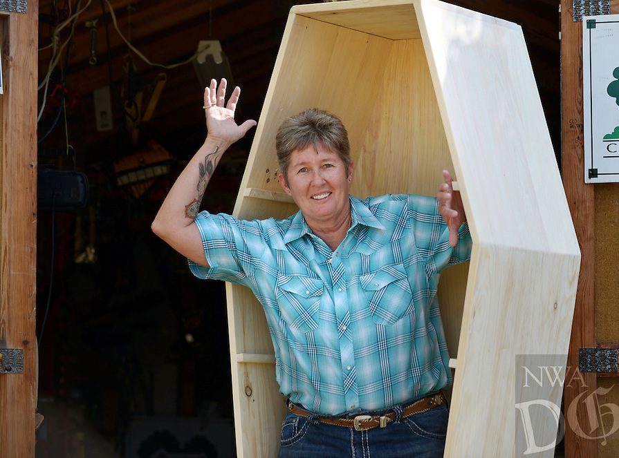NWA Democrat-Gazette/BEN GOFF @NWABENGOFF<br /> Cindy Jones, a founder and board member of the Northwest Arkansas Natural Burial Association, poses with a pine coffin on Monday Oct. 17, 2016 at her home in Rogers. Jones built the coffin, which can serve as a book shelf until needed, to be raffled off at the organization's inaugural Death Fest which runs Oct. 27-Nov. 1 in Fayetteville.