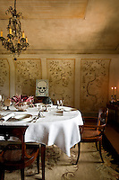 Little skeletons are used as placenames on a laid table in a dining room with delicate trompe l'oeils painted on the curved wall