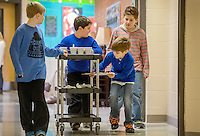 STAFF PHOTO JASON IVESTER --12/18/2014--<br /> Graham Hardin (from left), Logan Mullins, Theodore Haven and Strael (cq) Wolfe take a cart with hot chocolate to be delivered to classrooms on Thursday, Dec. 18, 2014, inside Sugar Creek Elementary School in Bentonville. Third-graders at the school sold hot chocolate and snacks to students and staff to raise money for the Northwest Arkansas Children's Shelter.