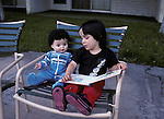 San Diego CA 2-yr-old girl, 1/2 latina reading book to her doll MR