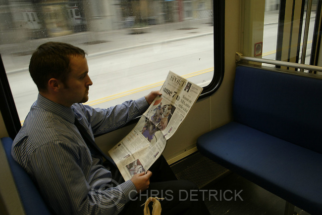 Salt Lake City, UT--31 Dec 1969--.  Corey Duncan reads the Sports section of The Tribune during his commute home on the TRAX train..Chris Detrick /Salt Lake Tribune.File #Trib Readers CD09