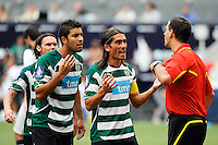 Carlos Saleiro (9) (L) and Pedro Mendes (6) (C)  of Sporting Clube de Portugal argue a call by referee Steven Depiero. Tottenham Hotspur F. C. and Sporting Clube de Portugal played to a 2-2 tie during a Barclays New York Challenge match at Red Bull Arena in Harrison, NJ, on July 25, 2010.