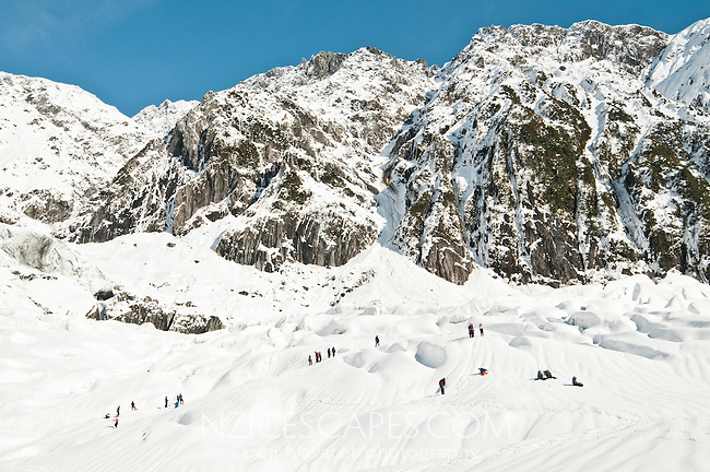 Group of guided tourists playing in fresh snow on Franz Josef Glacier, Westland National Park, West Coast, New Zealand