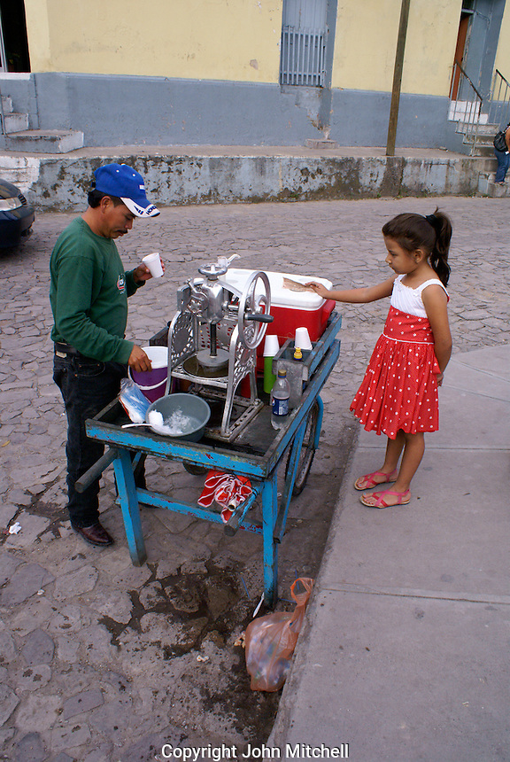 Young girl six to ten years old buying an ice cream from a street vendor, Santa Rosa de Copan, Honduras.