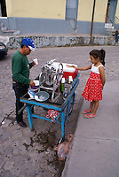 Young girl six to ten years old buying an ice cream from a street vendor, Santa Rosa de Copan, Honduras.