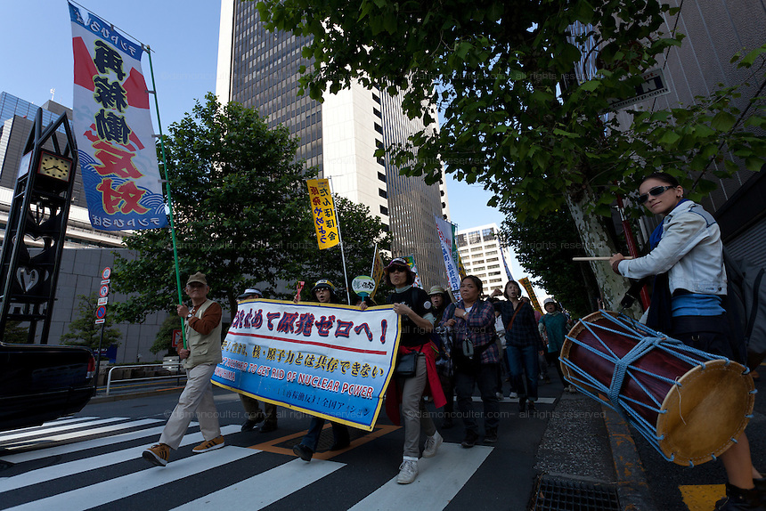A drummer accompanies anti nuclear protest marchers near Hibiya Park. Tokyo, Japan Sunday June 2nd 2013