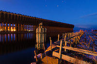 An evening view of the abandoned Lower Harbor iron ore loading dock and old wooden pilings that have become an iconic piece of Marquette, MI history.