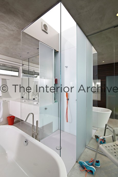 A contemporary white bathroom with a shower enclosure and a free-standing bath. A mirrored wall creates a sense of space to the room.