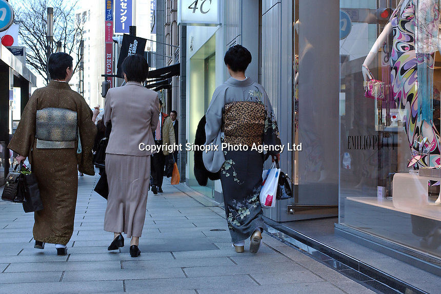 Shoppers wearing traditional Japanese kimino in the Ginza shopping district, Tokyo, Japan..