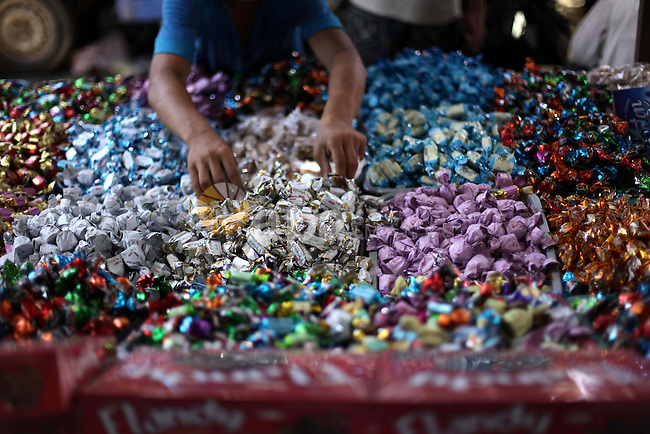 A Palestinian vendor displays the chocolate at the main market during preparations for the Eid Al-Fitr feast Gaza city on Aug 06, 2013, as Muslims over the world prepare to celebrate Eid al-Fitr, a three day holiday marking the end of the religious month of Ramadan in which believers abstain from food and water during daylight hours . Photo by Ashraf Amra