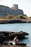 """Bagnanti sulla scogliera di Porto selvaggio con la Torre dell'Alto sullo sfondo - Reportage fotografico di Alessandro Caniglia, Alessandro De Matteis e Dario Luceri - Il Parco Naturale Regionale di Porto Selvaggio è situato lungo la costa ionica e ricade nel comune di Nardò (Lecce). Definito come """"area di notevole interesse pubblico"""" già nel 1939, è stato effettivamente istituito come Parco nel 2004. I suoi limiti sono compresi tra la baia di Frascone (a nord) e la Torre dell'Alto (a sud). Ha una estensione complessiva di circa 1000 ettari.Porto Selvaggio è una delle zone tra le più incontaminate del litorale Ionico, con un paesaggio caratterizzato da una pineta di ca. 300 ettari e da una macchia mediterranea ricca di acacee e ginestre..Lungo la costa sono presenti molte cavità carsiche, con varie insenature, grotte sommerse.Per gli amanti della natura il paesaggio è estremamente suggestivo in ogni stagione: molto silenzioso e rilassante in autunno, inverno e primavera, ricco di colori e festoso in estate, con il canto delle cicale che accompagna i visitatori lungo i sentieri e di tratti di scogliera che portano fino alla spiaggia. Il mare limpido e azzurro, con un fondale ricco di flora e fauna marina, è spesso meta di numerosi subacquei."""