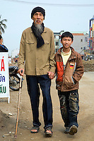 Vietnam. Ha Tay province. Lai Xa.  Portrait of an old man (grandfather) with a metal cane in hand walking and holding hands with with a young boy ( his grandson) wearing a german flag on his jacket. Construction site and widening of road. Urban development plan. Lai Xa is a typical hamlet (village) of the Red River delta region and is part of the Kim Chung commune located 15 km west of Hanoi. The peri-urban location is under increasing pressure of urbanization. 06.04.09 © 2009 Didier Ruef