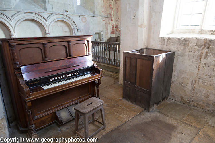 Building interior medieval church architectural feature, Inglesham, Wiltshire, England church organ and furniture with stone walls