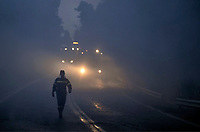 Pictured: A fireman is seen walking on the road followed by a fire truck.<br /> Re: A forest fire has been raging in the area of Kalamos, 20 miles north-east of Athens in Greece. There have been power cuts, country houses burned and children camps evacuated from the area.